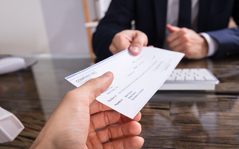 Payroll check being handed to employee